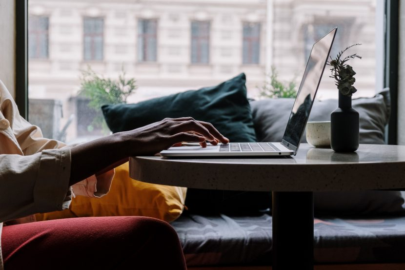 person in red pants sitting on a couch using a laptop